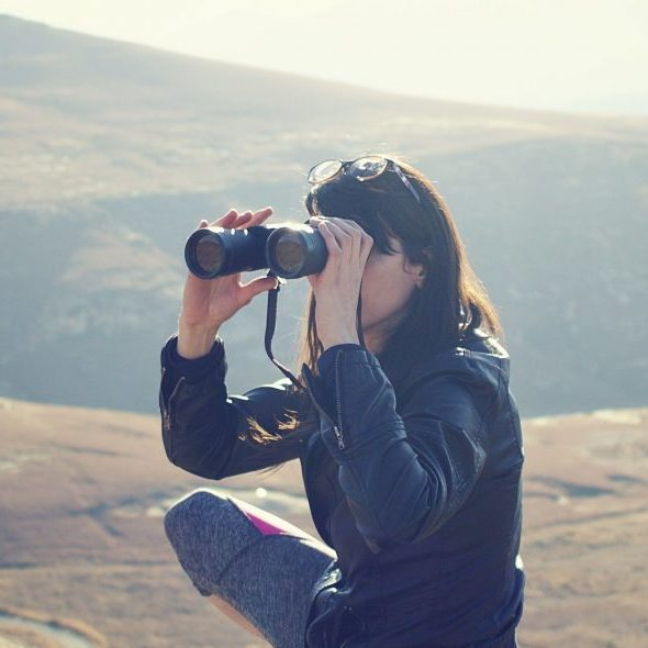 woman with binoculars in mountain